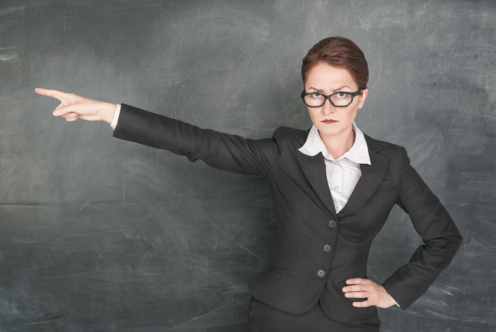 Angry teacher in glasses pointing out