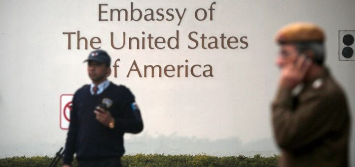 A U.S. embassy security guard (L) and an Indian policeman stand in front of the main gate of the embassy as the bulldozer (unseen) removes the security barriers, in New Delhi December 17, 2013. Indian authorities removed security barriers in front of the U.S. embassy in New Delhi on Tuesday apparently in retaliation for the arrest and alleged heavy-handed treatment of an Indian diplomat in New York. New Delhi police used tow trucks and bulldozers to remove the concrete barricades, which are used to restrict traffic on the road outside the embassy. REUTERS/Adnan Abidi (INDIA - Tags: POLITICS) - GM1E9CH1P9P01