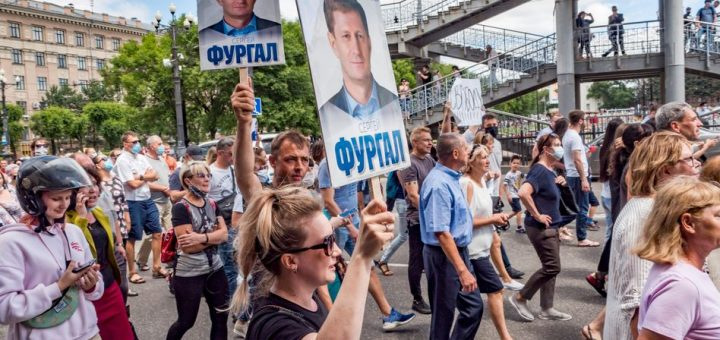 People hold up posters with portraits of Sergei Furgal during an unsanctioned protest in Khabarovsk, 6100 kilometers (3800 miles) east of Moscow, Russia, Saturday, July 11, 2020. Thousands of demonstrators in the Russian Far East city of Khabarovsk held a protest against the arrest of the region's governor on charges of involvement in multiple murders. (AP Photo/Igor Volkov)
